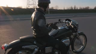 Young man sitting on motorcycle on the road at sunset, slow motion