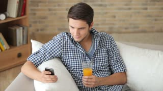 Young man sitting on sofa using cellphone and drinking juice