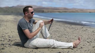 Young man sitting on the beach and chatting with tablet computer