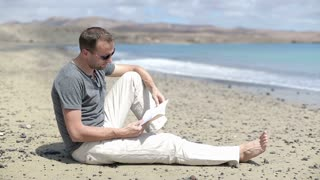 Young man sitting on the beach and reading book
