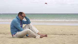 Young man sitting on the beach, slow motion shot at 60fps