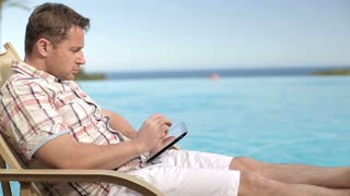 Young man taking photo with tablet by swimming-pool in hotel, steadicam