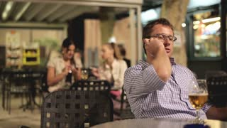 Young man talking on cellphone in the restaurant, evening