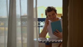 Young man talking on the phone with tablet PC in hands on hotel balcony