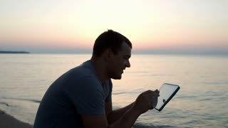 Young man typing message on pad sitting on beach and looking around