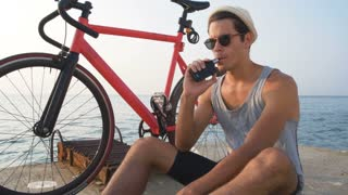 Young man vaping with his fixed gear bike beside him near the water