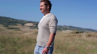 Young man walking at beautiful fields in Tuscany, steadycam shot