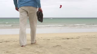 Young man walking on the beach, slow motion shot at 60fps