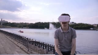 Young Man wearing virtual reality goggles outdoor