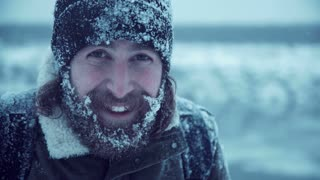 Young man with beard and long brown hair with snowbound hat, jacket and face smiling at camera