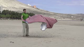 Young man with blanket after picnic on the beach, slow motion shot at 60fps