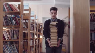 Young man with puzzled face standing in library holding high pile of books in front of him, camera zooming out to show many bookshelves