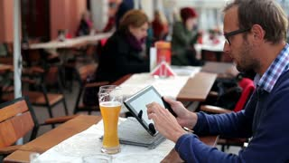 Young man with tablet computer drinking beer in the restaurant, outdoors