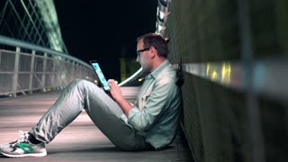 Young man with tablet computer on bridge in the city at night