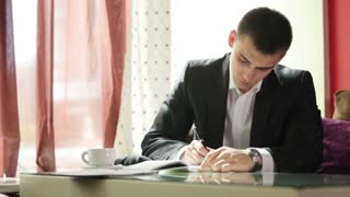 Young man writing something  and looking the time