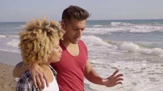 Young Mixed-Race Couple Standing On The Beach