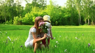 Young mother and child with flowers in the field. Look at Camera-1. Dolly