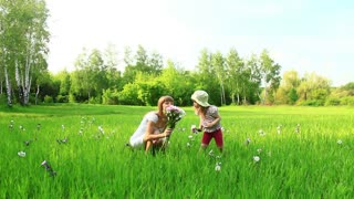Young mother and child with flowers in the field. Look at Camera. Dolly