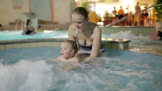 Young mother is playing with her son in the pool of the spa-salon.