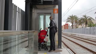 Young mother with her baby in a pram is entering the elevator at the Barcelona railway station.