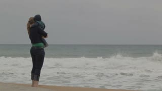 Young mother with her little son staying on the beach and looking at the sea waves. No faces visible.