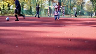 Young Mother With Her Son Running On Playing Field In Autumn