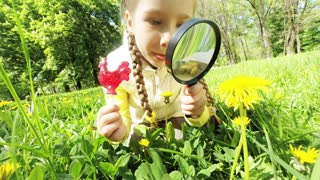 Young naturalist with lollipop studying flowers with a magnifying glass