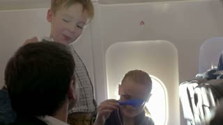 Young parents and child having fun during the flight. Boy playing with paper plane and then with fathers hand, mother playing with spades