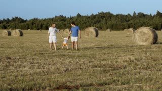 Young parents and son walking hand in hand among hay rolls in the field. Family time spending