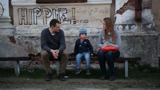Young parents and their little son sitting on the bench near worn grungy building with Hippie inscription on the wall