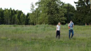 Young parents  and their little son walking in the wood together. Father spinning his little child. Outdoor family activities