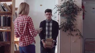 Young people students picking up books from different shelves in library and putting them in growing pile that unhappy guy carrying following camera