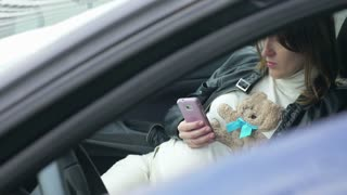 Young pregnant woman sitting in front seat of the parked car and using smart phone
