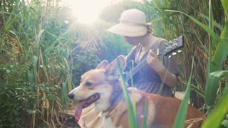 Young redhead girl playing guitar in park with corgi dog beside her