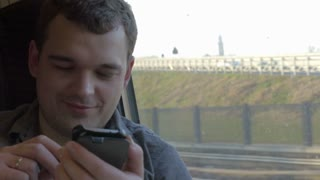 Young smiling man traveling by train and using smart phone. He sending message and looking out the window