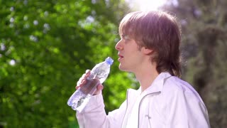 Young sports man drinking fresh water from the bottle in the sunny park refreshing himself. Slow motion. Filmed at 250 fps.
