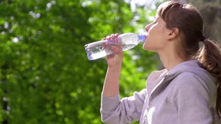Young sports woman drinking fresh water from the bottle in the sunny park refreshing herself. Slow motion. Filmed at 250 fps.