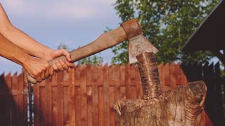 Young strong man is chopping wood outdoors. Slow Motion 240 fps. Lumberjack is working with a hatchet, preparing wood for the grill, fireplace, stove. Sunny back yard background. Household chores.
