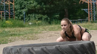 Young strong woman in sports bra and shorts doing tire flips in the park in slow motion