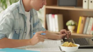 Young student sitting at table using laptop and eating chips