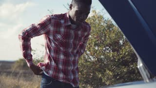 Young stylish african guy examining vehicle engine and turning up his sleeves