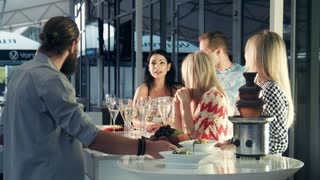 Young trendy people at a party in a modern club or hotel standing grouped around the bar counter with flutes of champagne chatting and socialising