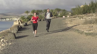 Young woman and businessman jogging on the beach, slow motion shot at 240fps