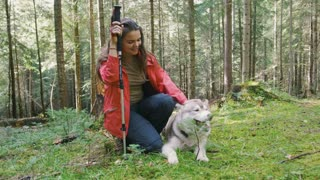 Young woman and cute siberian husky dog in forest