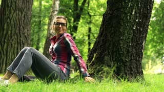 Young woman chilling out on grass in the park HD