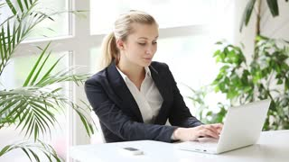 Young woman dressed in formal wear sitting at table at office and using laptop