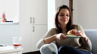 Young woman eating croissant and drinking juice at home