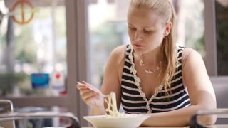 Young woman eating hot spaghetti, sometimes blowing on it.