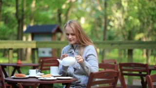 Young woman enjoying a pot of tea sitting alongside a tranquil lake at an outdoor restaurant table