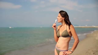 Young woman in bikini eating ice lolly on the beach